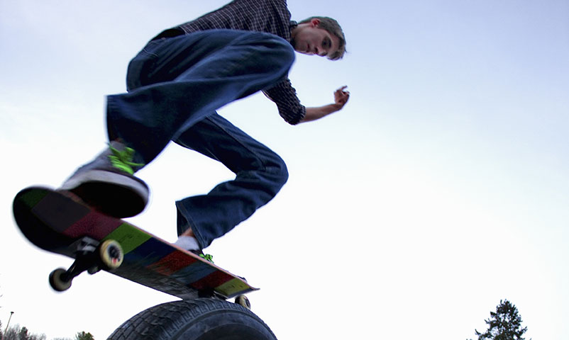 *** ROYALTY FREE - special pris *** Young man skateboarding on old tire. Keywords: Asphalt, Parking Lot, Sky, Blue, Day, Recreation, Skateboard, Stunt, Mid-Air, Jeans, Sweater, Casual Clothing, Skateboarding, Cool, Arms Outstretched, Showing Off, Skill, Fun, Talent, Youth Culture, Action, Agility, Sport, Urban Scene, Danger, Exhilaration, Leisure Activity, Extreme Sports, Looking Down, Balance, Tire, Carefree, Tree, Building Exterior, Sports Shoe, Motion, Vertical, Color Image, Above 18, Fish-Eye, Two Objects, One Person, Young Adult, 20-25 Years, Caucasian, Indoors. Collection Type: VCD, Collection Number: 303000, Collection Title: Then I Swallowed the Sun  Modelreleased: YES